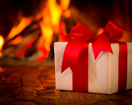 winter holiday: Christmas gift box on wood table against fireplace. Winter holiday concept