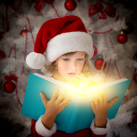 baby open present: Surprised child opening magic Christmas book. Xmas holiday concept