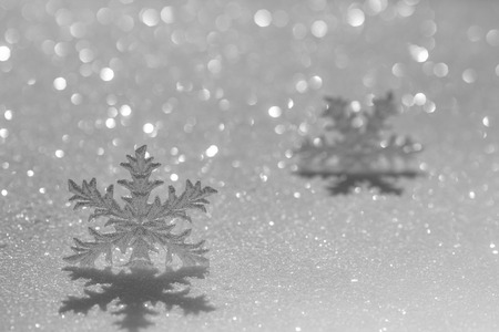 holiday background: Christmas ornament on snow against blurred lights background