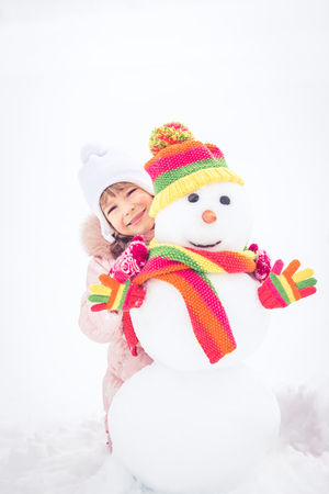 winter vacation: Happy child and snowman in winter park Stock Photo
