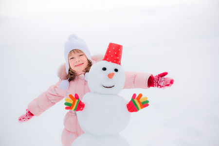 frosty the snowman: Happy child and snowman in winter park Stock Photo