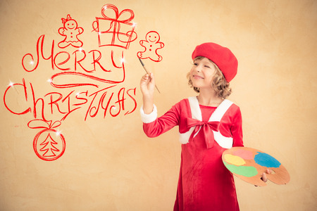 children painting: Child painting Christmas decorations. Kid playing at home. Xmas holiday concept