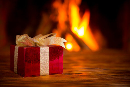 fireplace: Christmas gift box on wood table against fireplace. Winter holiday concept