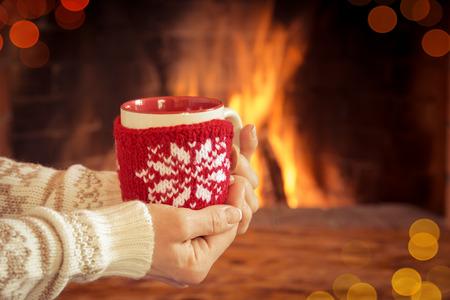 incendio casa: Manos de mujer que sostienen la taza de Navidad cerca de la chimenea. Concepto de vacaciones de invierno