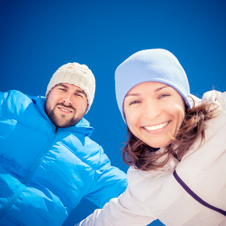winter couple: Happy couple having fun outdoors in winter against blue sky background Stock Photo