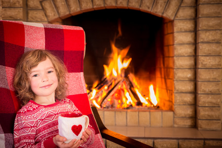 snug: Girl near fireplace. Valentines day at home. Winter holiday concept Stock Photo