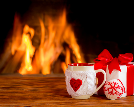 tazas de cafe: Cup of coffee near fireplace. Valentines day at home. Winter holiday concept Foto de archivo