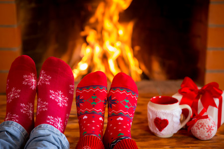 men socks: Couple near fireplace. Valentines day at home. Winter holiday concept Stock Photo