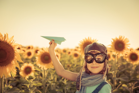 sun glasses: Happy child playing with toy airplane against summer sky background. Travel and vacation concept. Retro toned