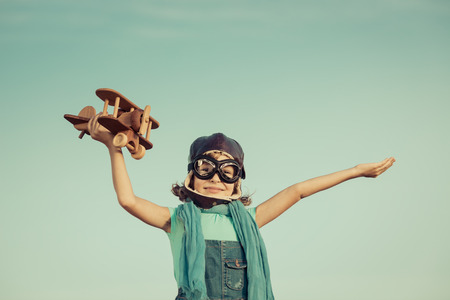 Happy child playing with toy airplane against summer sky background. Retro toned Stock Photo