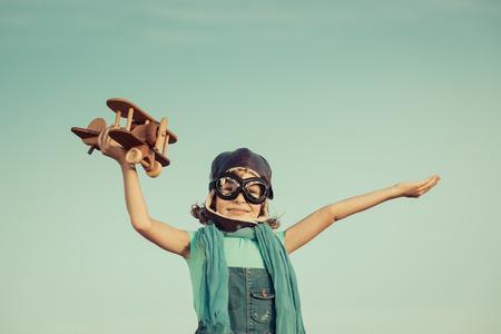 piloto: Niño feliz que juega con avión de juguete contra el fondo del cielo de verano. retro tonificado