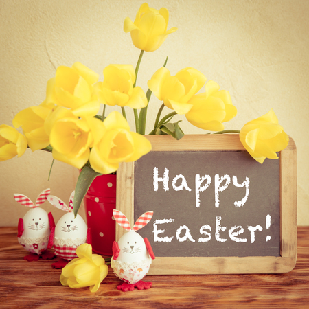 happy: Easter eggs, flowers and blackboard blank on wood table. Spring holidays concept