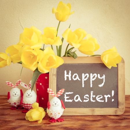 Ostereier, Blumen und Tafel leer auf Holz Tisch. Frühlingsferien Konzept