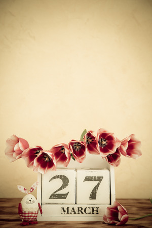 desk calendar: Basket of Easter eggs and flowers on wood table. Spring holidays 27 March. Retro toned image