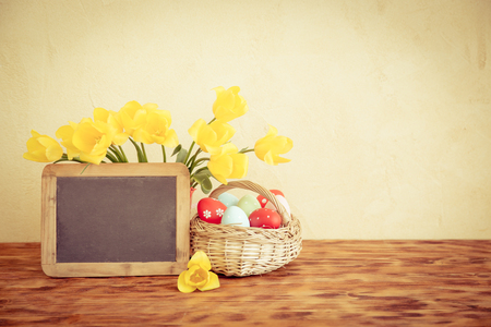 Easter eggs, flowers and blackboard blank on wood table. Spring holidays concept