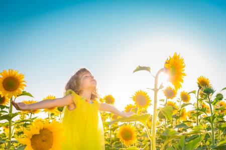 Glückliches Kind im Frühjahr Feld, die Spaß gegen den blauen Himmel im Hintergrund. Freiheit Konzept Standard-Bild