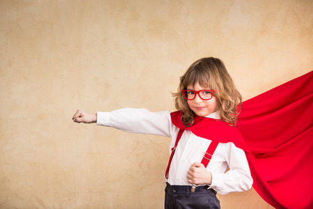 confident: Portrait of child superhero businessman in office. Success, creative and start up concept Stock Photo