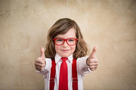confianza: negocios del niño confidente que muestra el pulgar hacia arriba. El concepto de éxito ganador de negocios Foto de archivo