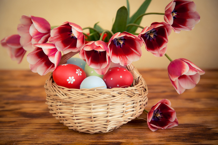 Easter eggs and flowers on wood table. Spring holidays concept