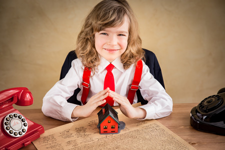 real business: Happy child businessman in office. Real estate business concept