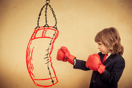 aggression: Businessman kid in red boxing gloves. Child punching on the drawn bag. Winner and success concept