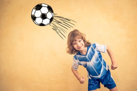 Het kind doet alsof hij een voetballer te zijn. Succes en winnaar begrip Stockfoto
