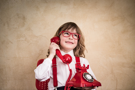 Happy child businessman with retro phone. Communication in business concept