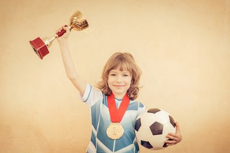 pretending: Child is pretending to be a soccer player. Success and winner concept