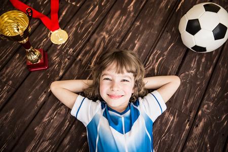 Het kind doet alsof hij een voetballer te zijn. Succes en winnaar begrip Stockfoto - 53562230