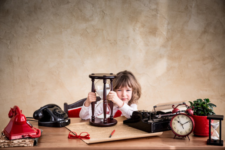 Portrait of child businessman with vintage hourglass in office. Time is money business concept Stock Photo