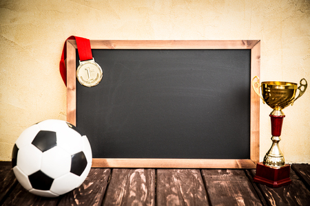 award: Blackboard with drawn soccer game strategy. Ball, trophy and medal Stock Photo
