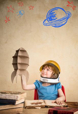 Kinder Astronaut mit Karton Spielzeug-Rakete. Kinder spielen zu Hause. Tag der Erde-Konzept