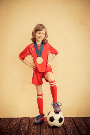 football play: Child is pretending to be a soccer player. Success and winner concept