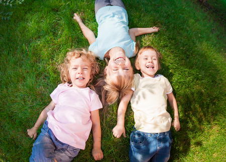 family in park: Group of happy children playing outdoors in spring park. Top view portrait Stock Photo