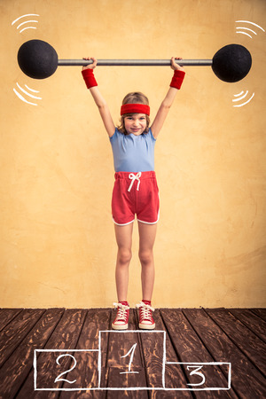 strong growth: Funny strong child with barbell. Girl power and feminism concept. Sport fitness success winner kid