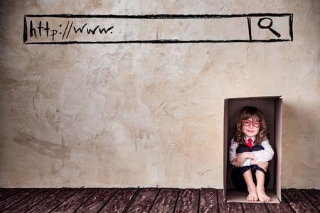 Portrait d'homme d'affaires de l'enfant dans la boîte de cardboadr. Pensez à l'extérieur du concept boîte business Banque d'images