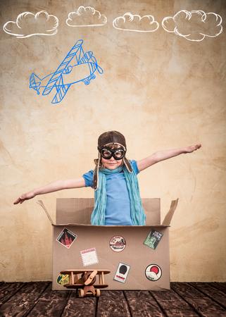 子がパイロットになるふりをしてください。子供が自宅で再生します。旅行、自由と想像力の概念 写真素材