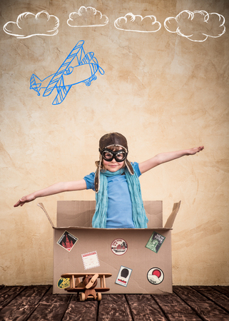 Child is pretending to be a pilot. Kid playing at home. Travel, freedom and imagination concept