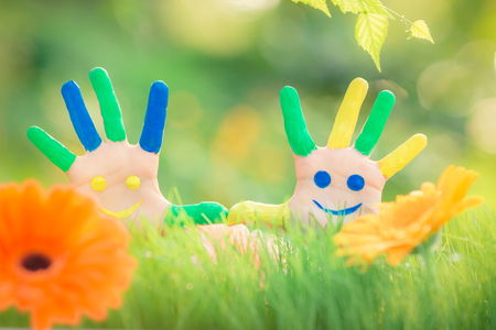 Happy child with smiley on hands against green spring background