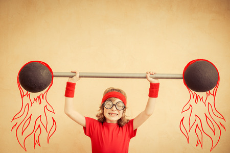 humor: Funny strong child with barbell. Girl power and feminism concept. Sport fitness kid