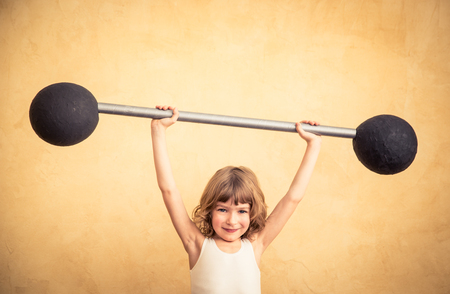 Funny strong child with barbell. Girl power and feminism concept. Sport fitness success winner kid