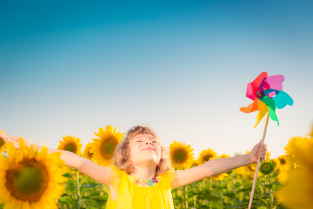 wellness environment: Happy child having fun in spring field against blue sky background. Freedom concept