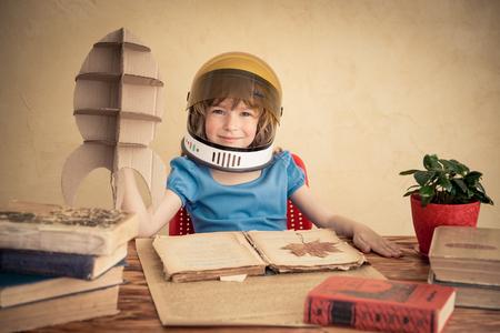 Kid astronaut met kartonnen speelgoed raket. Spelen van het kind thuis. Earth Day concept