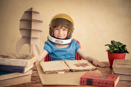 Kid astronaut with cardboard toy rocket. Child playing at home. Earth day concept