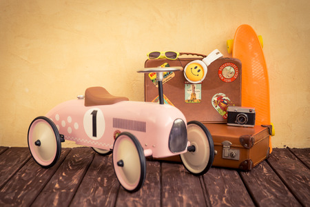 Vintage toy car and suitcase. Travel and summer vacation concept
