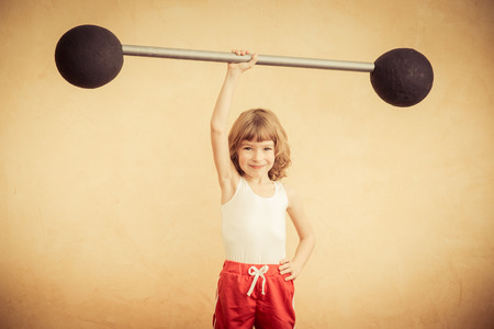 child sport: Funny strong child with barbell. Girl power and feminism concept. Sport fitness success winner kid