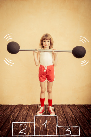 feminism: Funny strong child with barbell. Girl power and feminism concept. Sport fitness success winner kid