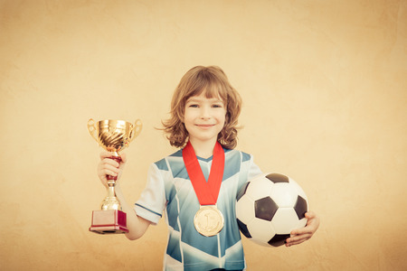 child portrait: Child is pretending to be a soccer player. Success and winner concept