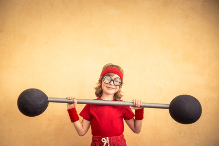 Funny strong child with barbell. Girl power and feminism concept. Sport fitness kid