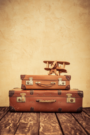 vintage travel: Vintage toy airplane and suitcase. Summer vacation and travel concept